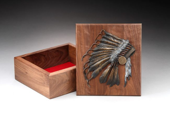 "War Bonnet Jewelry Box 4""H x 10""L x 9""W Limited Edition of 12 A ""war bonnet"" showing wrapped eagle feathers, polished disc, and hanging ermine skins all cast in bronze cover the lift off lid of this black walnut box."