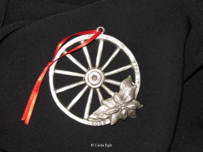 "Wagon Wheel - Western Christmas Ornament Linda Egle. These Christmas ornaments are of the western flavor. The images are all worked over a 3 1/4"" rope circle and cast in pewter."