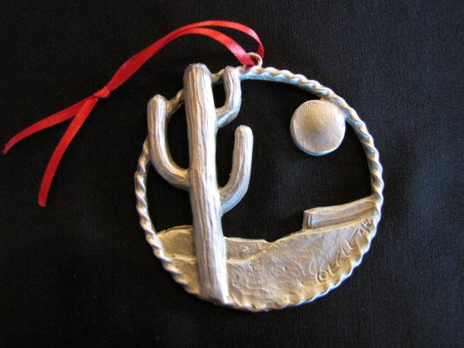 "Desert Cactus - Western Christmas Ornament Linda Egle. These Christmas ornaments are of the western flavor. The images are all worked over a 3 1/4"" rope circle and cast in pewter."